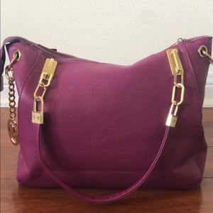 Faux leather purple purse with gold hardware.